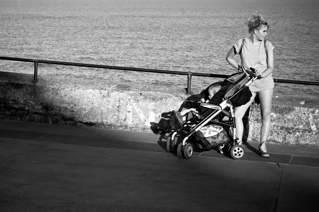 Young mum with pushchair at seaside