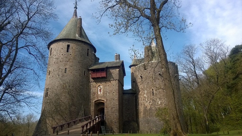 Castle Coch against a blue sky with trees in the foreground